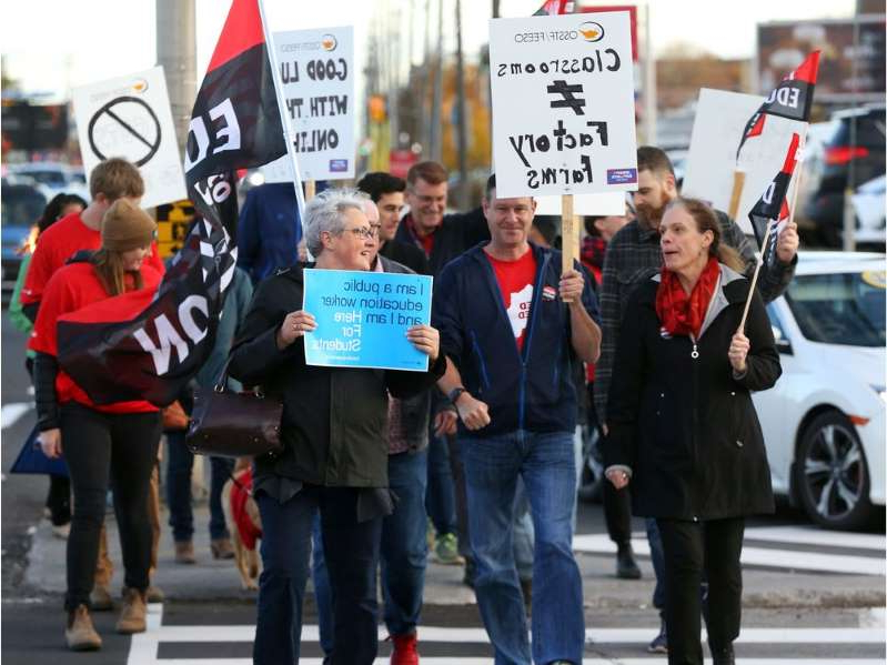 a group of people walking down a street holding a sign: Protest on Merivale Rd in Ottawa by teachers who are in contract negotiations and fighting increases to class sizes, October 25, 2019.