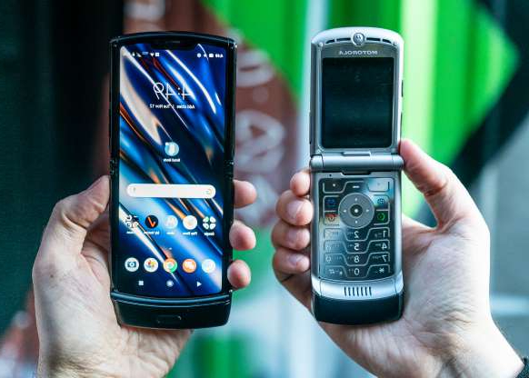 a hand holding a cellphone: The original Motorola Razr V3 from 2004, left, is narrower than its new reinvention as a smartphone.