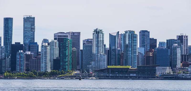 a large body of water with a city in the background:  Vancouver has seen a significant drop in the commercial property tax rate.