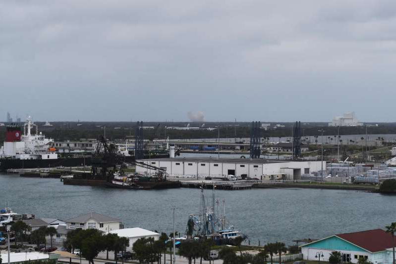 a large ship in a body of water: From Port Canaveral several miles away, the Crew Dragon abort engine test firing could be seen as a sudden cloud of billowing exhaust on the horizon.