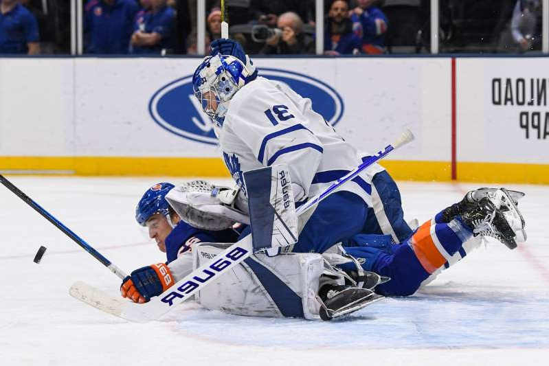 a person skiing on the snow: Toronto Maple Leafs goaltender Frederik Andersen (31) makes a save as New York Islanders center Anders Lee (27) is knocked down during the second period at Nassau Veterans Memorial Coliseum on November 13, 2019.