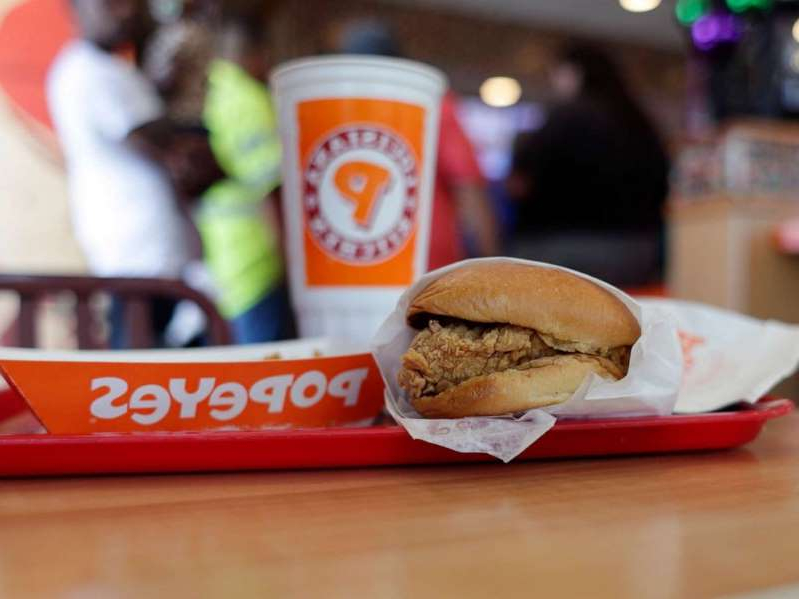 a sandwich sitting on top of a wooden table: In this photo taken on Aug. 22, 2019, a chicken sandwich is seen at a Popeyes as guests wait in line, in Kyle, Texas.