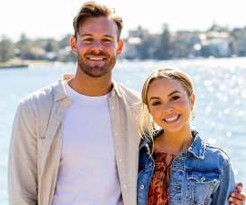a smiling man and woman posing for a picture: Since winning 'The Bachelorette' Australia 2019, many fans have wondered whether Angie and Carlin are still together to this day.