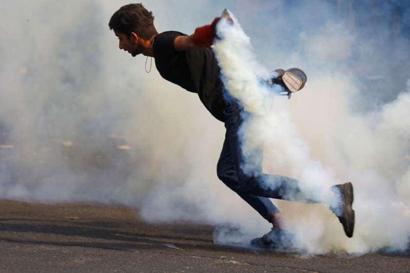 An Iraqi demonstrator runs as he carries a tear-gas canister during ongoing anti-government protests in Baghdad, Iraq November 14, 2019. REUTERS/Alaa al-Marjani