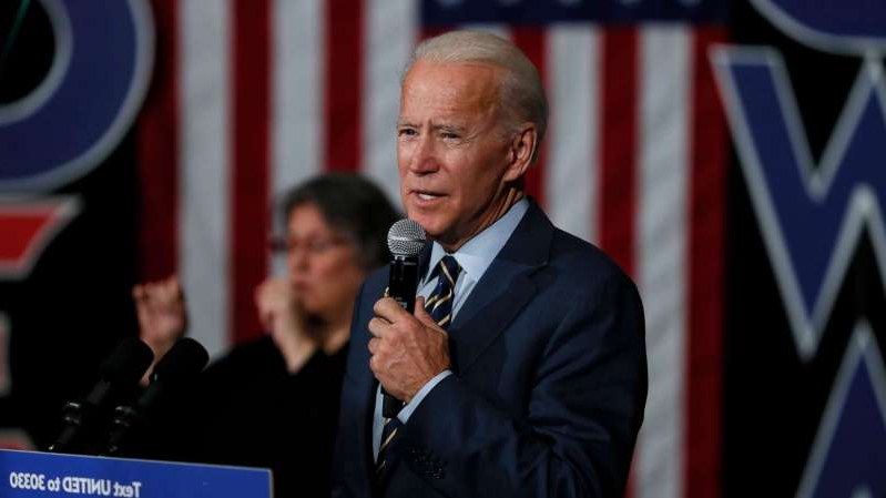 Joe Biden wearing a suit and tie talking on a cell phone: Democratic presidential candidate former Vice President Joe Biden speaks during a town hall meeting, Monday, Nov. 11, 2019, in Oskaloosa, Iowa. (AP Photo/Charlie Neibergall)