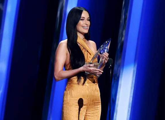 Slide 4 of 18: NASHVILLE, TENNESSEE - NOVEMBER 13: (FOR EDITORIAL USE ONLY) Kacey Musgraves accepts an award onstage during the 53rd annual CMA Awards at the Bridgestone Arena on November 13, 2019 in Nashville, Tennessee. (Photo by Terry Wyatt/Getty Images,)