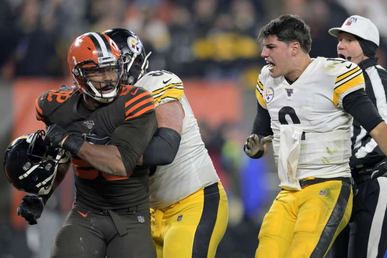 a group of baseball players standing on top of a field: Myles Garrett reacts after swinging a helmet at Steelers quarterback Mason Rudolph in the fourth quarter of Thursday's game. (AP Photo/David Richard)