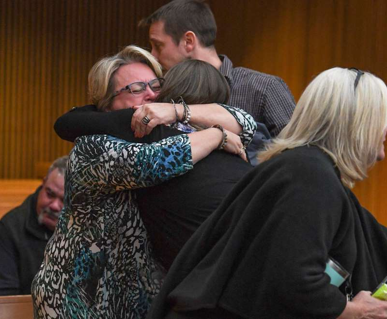 a group of people looking at a phone: Townville Elementary and families affected by the shooting from 2016 hug after Jesse Osborne was sentenced by Judge Lawton McIntosh for life at the sentence-related hearing at the Anderson County Courthouse Thursday, November 14, 2019.