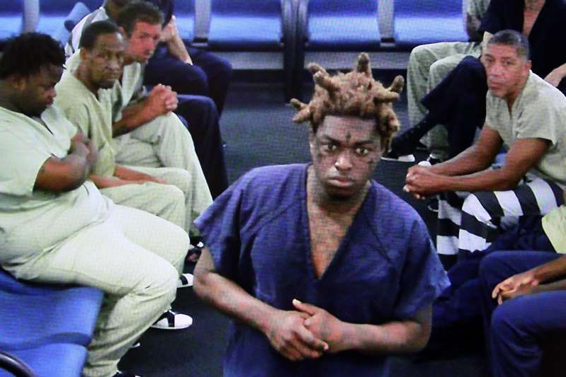 a group of people sitting at a table: Attorney Brad Cohen Rapper Kodak Black, whose real name is Dieuson Octave, appears via CCTV in magistrate court on Friday, Jan. 19, 2018. Octave, 20, of Pembroke Pines, was arrested on seven felony counts, including grand theft of a firearm, possession of a weapon by a convicted felon, marijuana possession and child neglect.