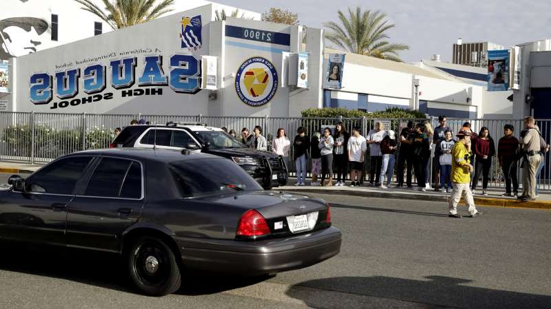 a group of people standing in front of a car: Students stand outside of Saugus High School after a mass shooting.