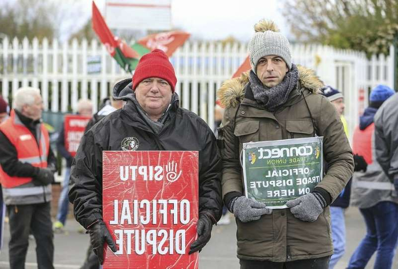 a group of people standing in front of a sign: James Daly and Brian Keating with fellow staff members on the picketline outside the SK Biotek plant in Swords  Picture; Gerry Mooney