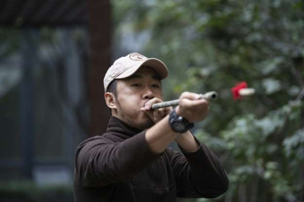 a person holding a baseball bat: Chinese pet detective Sun Jinrong tests his blowdart as he prepares to search for a missing cat in a residential compound in Beijing