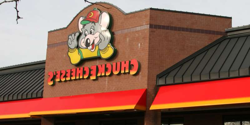 a sign above a storefront on a brick building: Old Chuck E. Cheese restaurant exteriors featured red and yellow awnings with a large cartoon mouse.