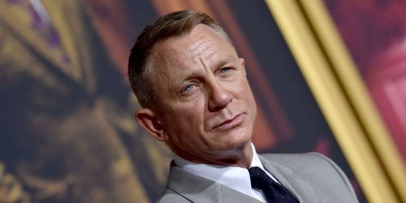 Daniel Craig wearing a suit and tie looking at the camera: At the Knives Out premiere, Daniel Craig's rigid 007 suit became a lot less James Bond, and a lot more fluid.
