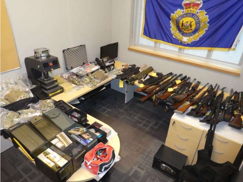 a cluttered desk with a computer on a table: An Ontario Provincial Police handout photo of weapons, including an inert (non-functioning) rocket launcher, am munition and drugs seized during a raid at a Christie Street residence on Thursday.