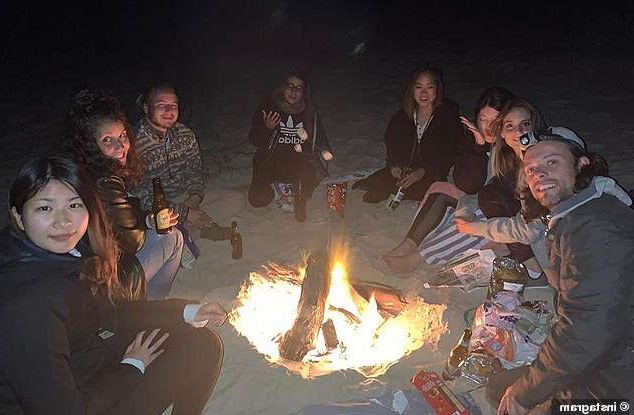 a group of people standing around a fire: Now people who have followed his case closely claim the answer may be in social media pictures shared on the night he vanished and the following morning. Pictured: Image from Tallow Beach on May 31