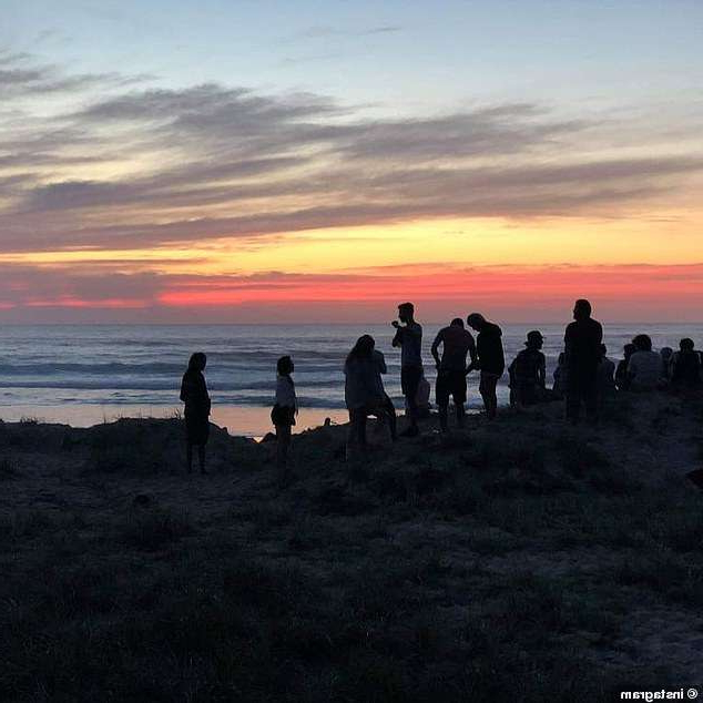 a group of people standing on a beach with a sunset in the background: One woman who shared images from a few weeks prior to Theo's disappearance said doofs are common for backpackers. Pictured: Tallow Beach doof from April 2019