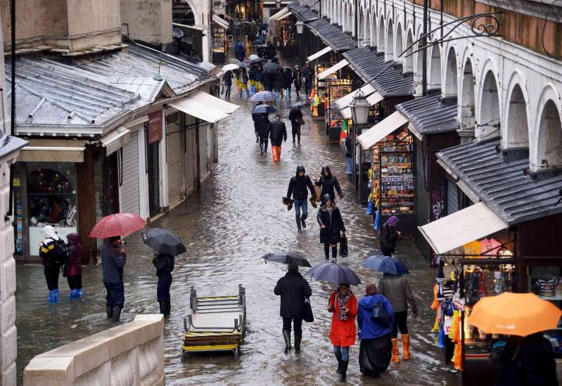 a group of people walking in the rain: People walk in the flooded street near Rialto bridge in Venice. (Filippo Monteforte/AFP via Getty Images)