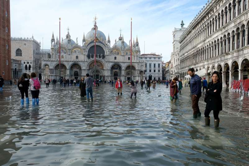 a group of people walking in the water: Tourists walk in St. Mark's Square after days of severe flooding in Venice