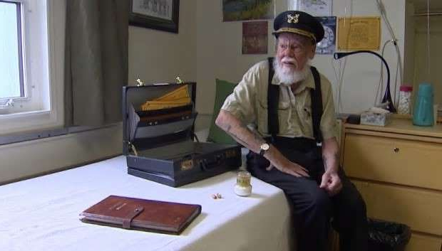 a man standing in front of a counter: Captain Dick Stevenson sits at home in Whitehorse in 2017 with some 'Sourtoe Cocktail' memorabilia — old certificates, a registry of club members and a couple of dried human toes.