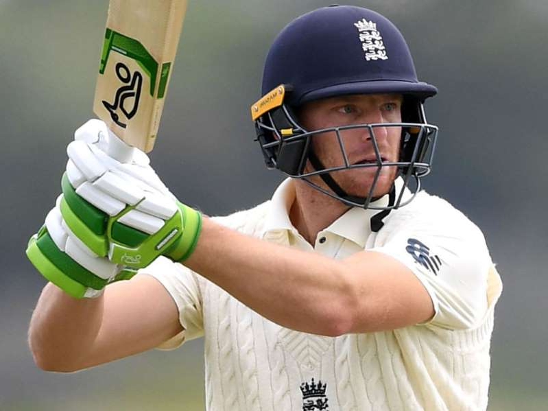 a man wearing a helmet holding a baseball bat: Jos Buttler scored an unbeaten 88 as England rallied against New Zealand A