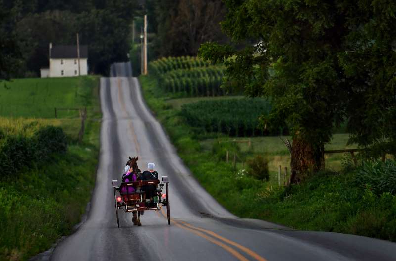 a person riding a motorcycle on the side of a road: Tensions over an essential aspect of Amish life — horse-drawn buggies — have roiled two Pennsylvania communities.