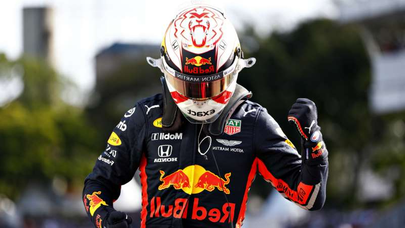 a person wearing a helmet: Max Verstappen celebrates his pole position