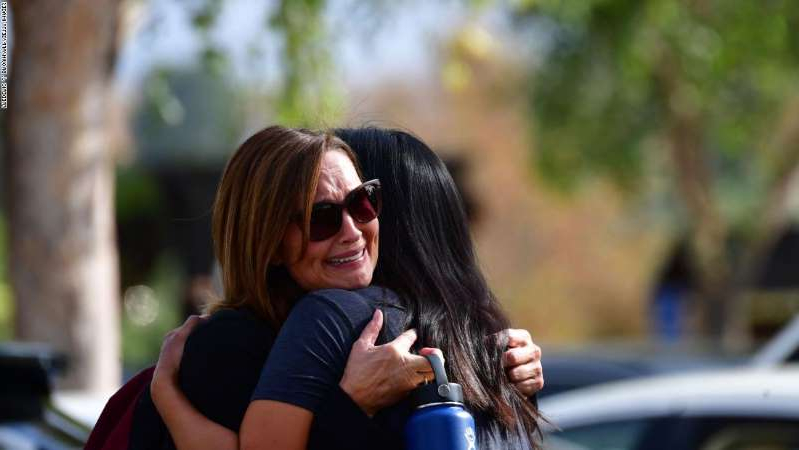a woman talking on a cell phone: Women embrace in Central Park after a shooting at Saugus High School in Santa Clarita, California on November 14, 2019.