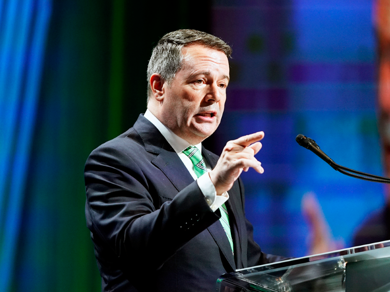 Jason Kenney standing on a stage: Alberta Premier Jason Kenney speaks at the Rural Municipalities of Alberta 2019 Fall Convention in Edmonton on Nov. 15, 2019.