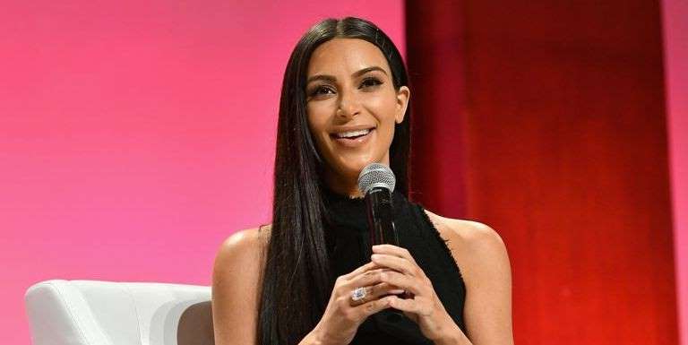 Kim Kardashian wearing a black dress: Kim Kardashian poses with engagement ring that was reportedly stolen in Paris robbery in 2016 in new KKW perfume campaign and fans are super confused