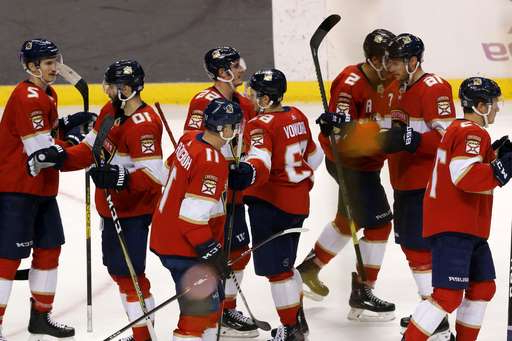a group of baseball players that are standing in the snow: Florida Panthers players celebrate their win over the New York Rangers in an NHL hockey game, Saturday, Nov. 16, 2019, in Sunrise, Fla. (AP Photo/Joe Skipper)