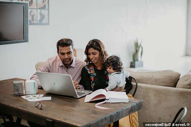 a group of people sitting at a table using a laptop: The couple were hoping to be closer to their three boys at home, so decided to pursue entrepreneurship