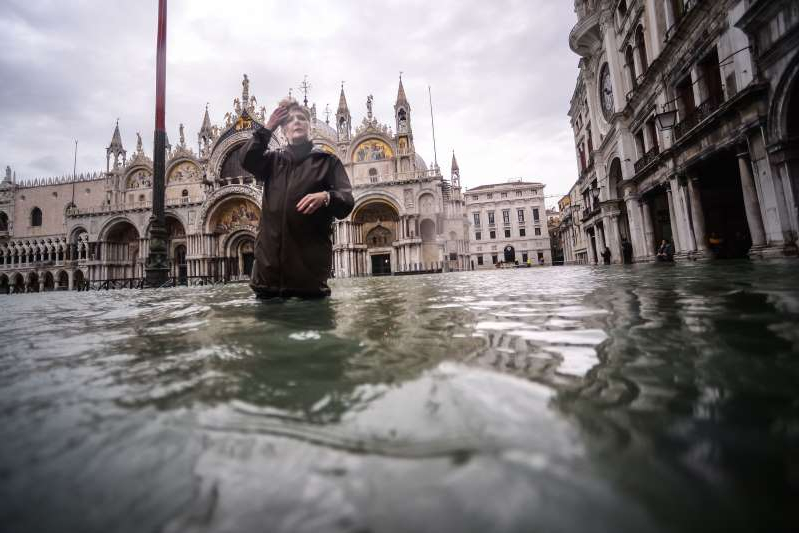 a large building with a clock on the side of a river: A general view shows a woman walking across the flooded St. Mark's Square, by St. Mark's Basilica (Rear) on November 15, 2019 in Venice, two days after the city suffered its highest tide in 50 years. — Flood-hit Venice was bracing for another exceptional high tide on November 15, as Italy declared a state of emergency for the UNESCO city where perilous deluges have caused millions of euros worth of damage.