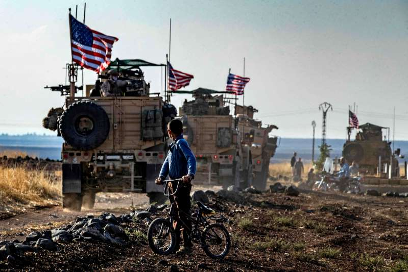 a man riding a bike down a dirt road: Image: A Syrian boy looks at a U.S. convoy patrolling near the Turkish border on Oct. 31, 2019.