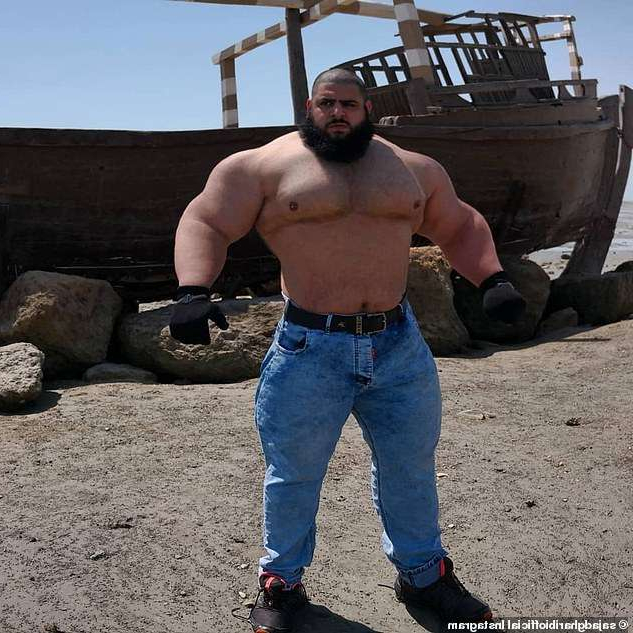 a man that is standing in the sand: Gharibi, meanwhile, has a cult following on social media where he posts weightlifting shots (pictured)