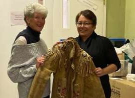 a person standing in front of a group of people posing for the camera: Laura Chaboyer, left, and Sharon Leveque with a beaded jacket that has been located in Kelowna for decades. Chaboyer and Leveque met in British Columbia earlier this week so a group from the Cumberland House Cree Nation could repatriate artifacts that have been in the Leveque family for generations.