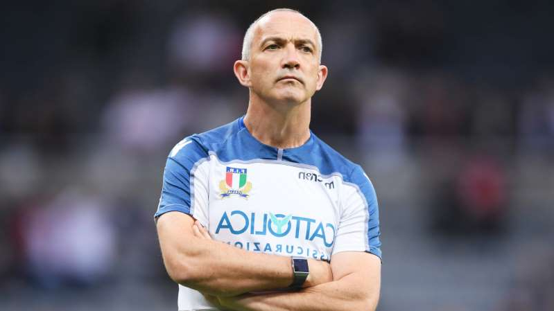 Conor O'Shea in a blue uniform holding a ball: Conor O'Shea, who has stepped away from Italy