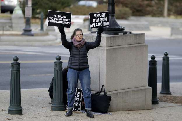 Slide 10 of 52: A demonstrator holds signs outside Longworth House Office Building, Friday, Nov. 15, 2019, on Capitol Hill in Washington, where former U.S. Ambassador to Ukraine Marie Yovanovitch is scheduled to testify to the House Intelligence Committee in the second public impeachment hearing of President Donald Trump's efforts to tie U.S. aid for Ukraine to investigations of his political opponents. (AP Photo/Julio Cortez)