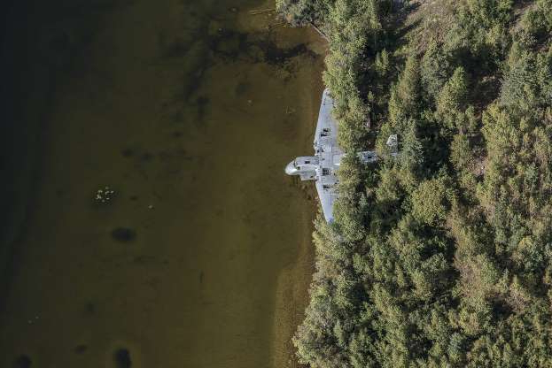 Slide 13 of 28: The abandoned plane rots away quietly as it rests on the side a lake in Canada.
