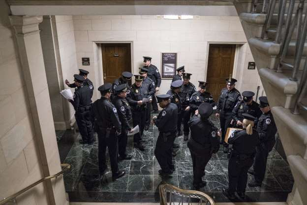 Slide 28 of 52: WASHINGTON, DC - NOVEMBER 13: Capitol Police gather before the House Intelligence Committee hearing in the Longworth House Office Building on Capitol Hill November 13, 2019 in Washington, DC. In the first public impeachment hearings in more than two decades, House Democrats are trying to build a case that President Donald Trump committed extortion, bribery or coercion by trying to enlist Ukraine to investigate his political rival in exchange for military aide and a White House meeting that Ukraine President Volodymyr Zelensky sought with Trump.