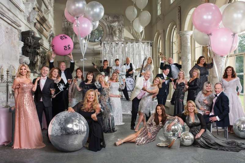 a group of people standing in front of a statue: All the winners gathered for a gala ball to celebrate 25 years of the National Lottery