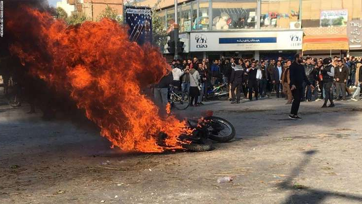 a group of people walking in front of a crowd: Iranian protesters gather around a burning motorcycle during a demonstration against an increase in gasoline prices in the central city of Isfahan, on November 16, 2019. - One person was killed and others injured in protests across Iran, hours after a surprise decision to increase petrol prices by 50 percent for the first 60 litres and 300 percent for anything above that each month, and impose rationing. Authorities said the move was aimed at helping needy citizens, and expected to generate 300 trillion rials ($2.55 billion) per annum. (Photo by - / AFP) (Photo by -/AFP via Getty Images)