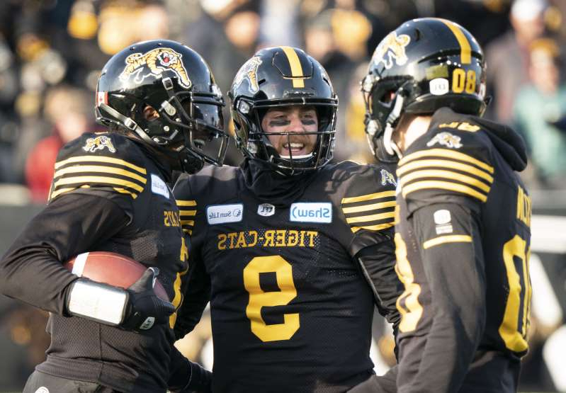 a person wearing a helmet: Hamilton Tiger-Cats quarterback Dane Evans (9) celebrates with teammates during second half of the CFL's Eastern Final against the Edmonton Eskimos in Hamilton, Ont. on Sunday, Nov. 17, 2019.