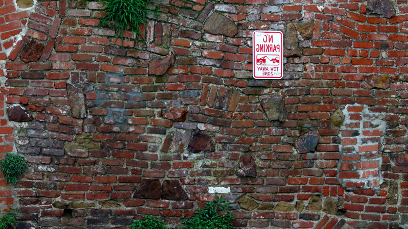 a sign on a brick wall: *Slaps brick wall* This bad boy can fit so many mpg in it (Photo: a href=
