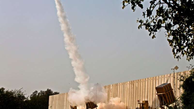a train on a track with smoke coming out of it: A missile from Israel's Iron Dome defense system was fired on Wednesday to intercept rocket fire from the Gaza Strip.