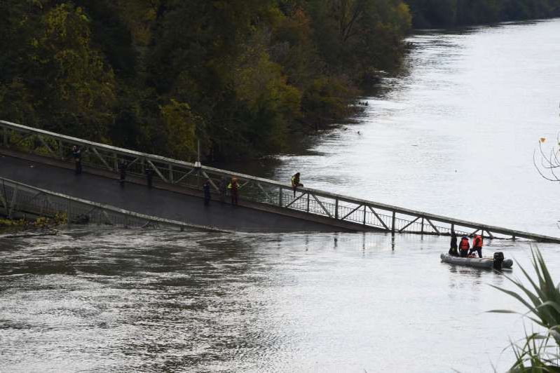 Rescuers sail near a suspension bridge which collapsed on November 18, 2019 in Mirepoix-sur-Tarn, near Toulouse, southwest France. - A 15-year-old girl was killed after a suspension bridge over a river collapsed on November 19, causing a car, a truck and possibly a third vehicle to plunge into the water, local authorities said. Four people were rescued but several others were feared missing after the collapse of the bridge linking the towns of Mirepoix-sur-Tarn and Bessieres, 30 kilometres (18 miles) north of the city of Toulouse, said fire service and local security chief Etienne Guyot. (Photo by ERIC CABANIS / AFP) (Photo by ERIC CABANIS/AFP via Getty Images)