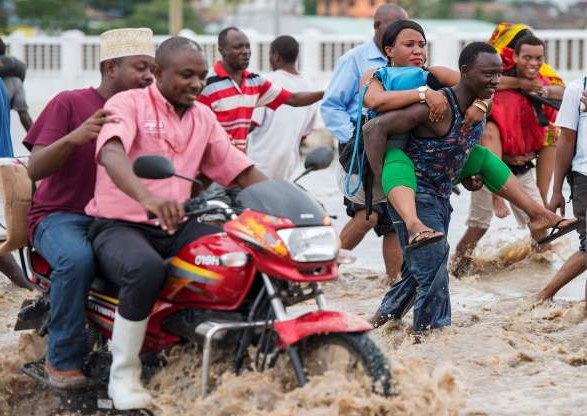 Slide 13 of 25: Pedestrians pay for piggy-back rides across flooded Morogoro Road in Dar es Salaam, Tanzania, on May 7, 2015. The Tanzania Meteorological Agency warned of 50mm of rainfall on May 6 and 7 due to a low pressure system developing in the Indian Ocean.  AFP PHOTO / DANIEL HAYDUK        (Photo credit should read Daniel Hayduk/AFP/Getty Images)