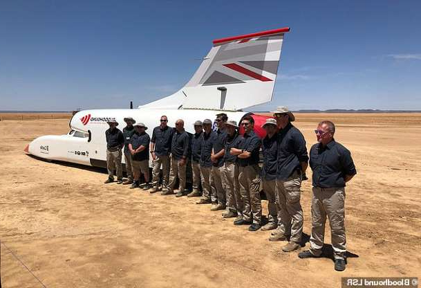 a group of people standing around a plane: The jet-powered vehicle was flown to Johannesburg and then transported another 570 miles to the desert where tests have taken place