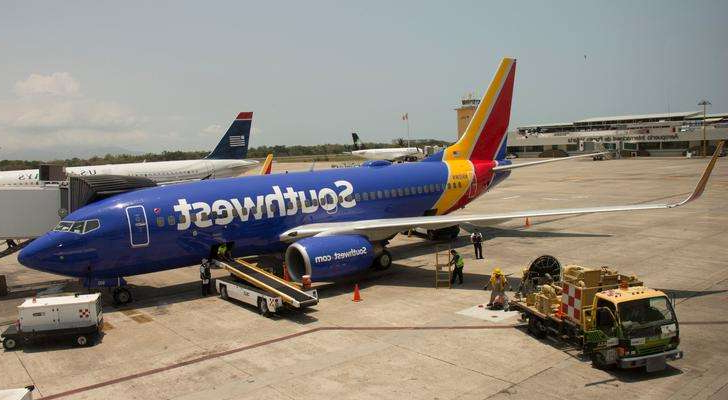 a large passenger jet sitting on top of a tarmac at an airport: A Southwest Airlines Boeing 737 on the tarmac in Puerto Vallarta, Mexico
