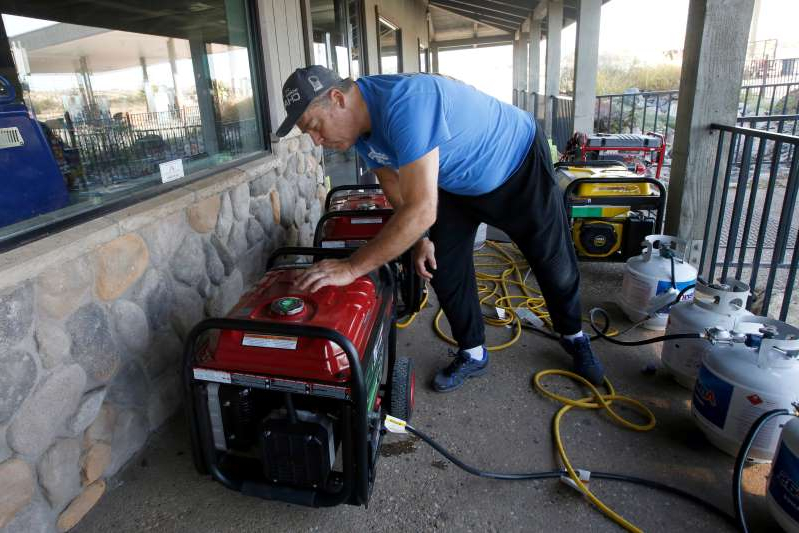 a man sitting on a table: Brian Boyd checks one of the generators used to provide power at the Clear Creek Crossing store near Paradise, Calif., on Oct. 24, 2019. The Pacific Gas & Electric Co. cut power to 17 counties in Northern California to help prevent wildfires caused by downed power lines. Boyd said generators were brought to the store to provide power to the refrigerators and to provide some service to area residents.